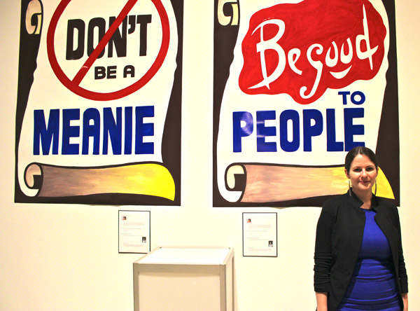 Artist Corrie Baldauf, with a pair of her signature signs.
