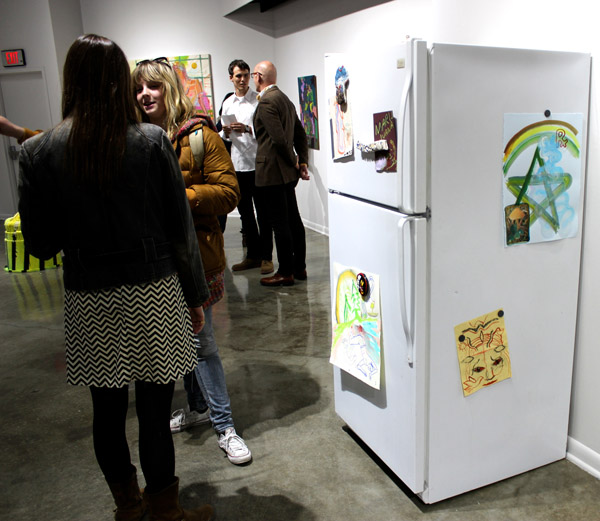 """Fridge, with drawing by Katrina Fimmel, magnets by Mike Swaney, and """"Freezer"""" by Rajewski inside, alongside opening night refreshments."""